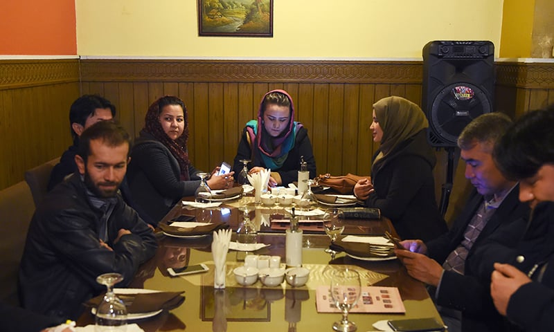 Afghan men and women wait to eat their lunch at a restaurant in Kabul. ─ AFP
