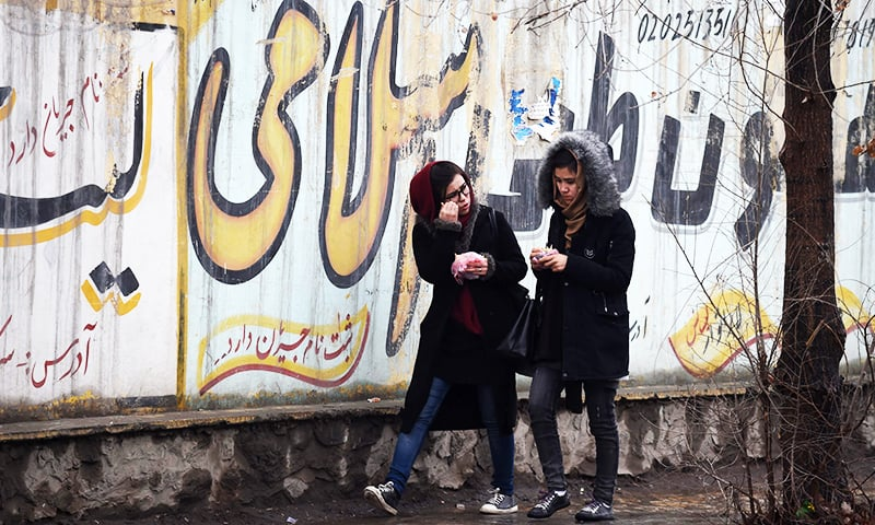 Afghan girls walk next to graffitis on a wall in Kabul. ─ AFP