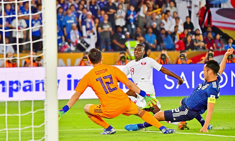 Qatar's forward Almoez Ali (C) attempts a shot as he is marked by Japan's defender Maya Yoshida (R) and Japan's goalkeeper Shuichi Gonda (L). — AFP