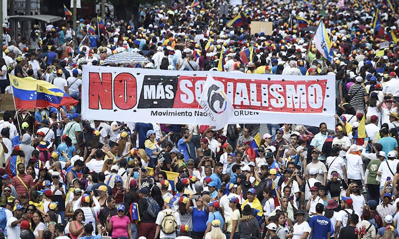 """Opposition supporters hold a banner reading """"No More Socialism"""" during a gathering with Venezuelan opposition leader Juan Guaido, in Caracas on February 2, 2019. — AFP"""