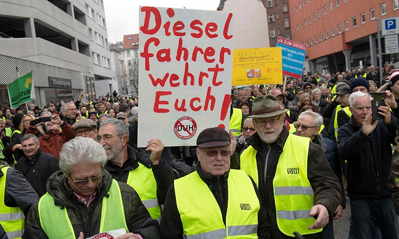 "Protesters wearing yellow vests hold up a banner reading ""Diesel drivers resist!"" during a demonstration against Germany's first comprehensive driving ban for older diesels, in Stuttgart, southwestern Germany, on February 2, 2019. — AFP"