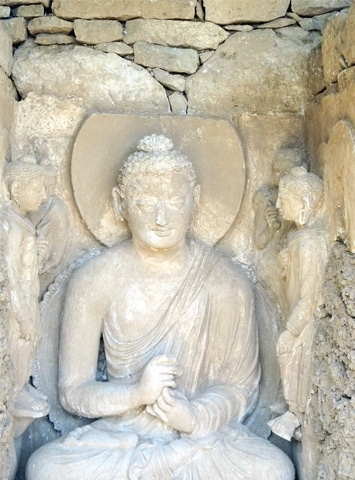 A statue of Buddha in the meditation pose made of stucco.