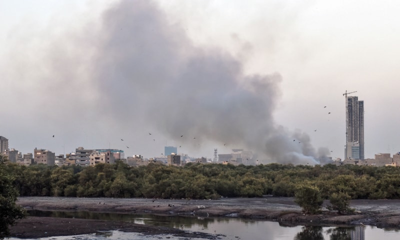 Smoke spotted from behind the thinning mangroves on the Hijrat Colony side of the Mai Kolachi Bypass last week.