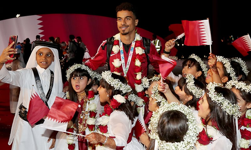 Qatar's forward Akram Afif (up) poses for a photograph at Doha airport. — AFP