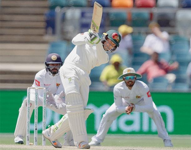 CANBERRA: Australian batsman Usman Khawaja drives during the second Test against Sri Lanka on Sunday.—AP