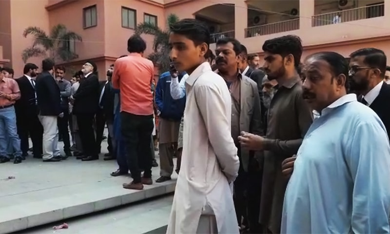 Onlookers surround the body at the site of the incident on the Sindh High Court premises in Karachi. ─ Screengrab