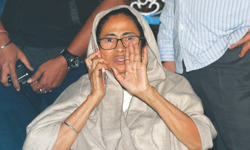 Mamata Banerjee, chief minister of West Bengal, speaks on her mobile phone as she sits in a protest against an attempted raid by India's Central Bureau of Investigation officials on the residence of Kolkata police commissioner.—Reuters