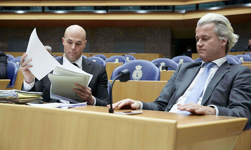 A picture taken on April 4, 2013 at the Dutch parliament in The Hague shows PVV party members Joram van Klaveren (L) and Geert Wilders (R). — AFP