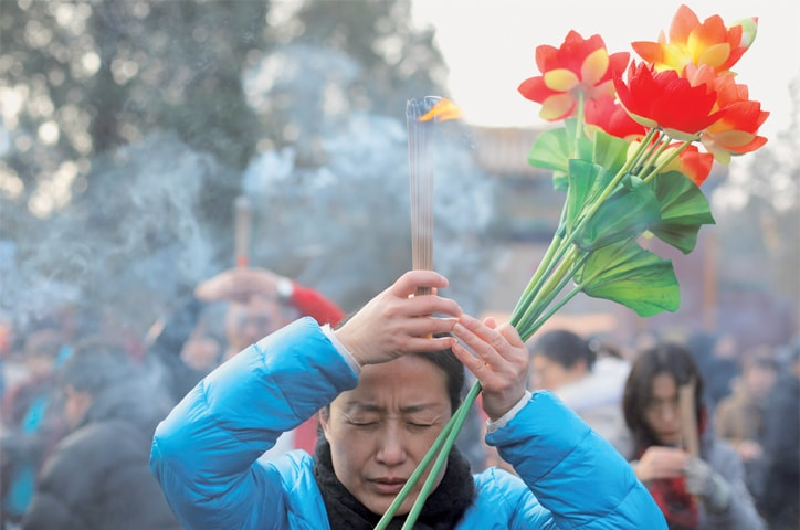 Beijing: A woman burns incense sticks and prays at a temple on the first day of the Lunar New Year on Tuesday.—Reuters