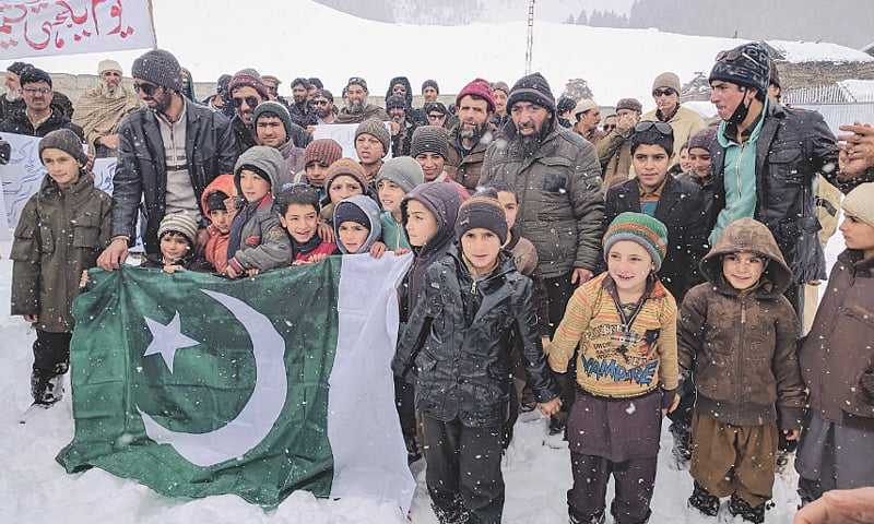Children hold the national flag at a Kashmir Solidarity Day rally during snowfall in Astore.—Dawn