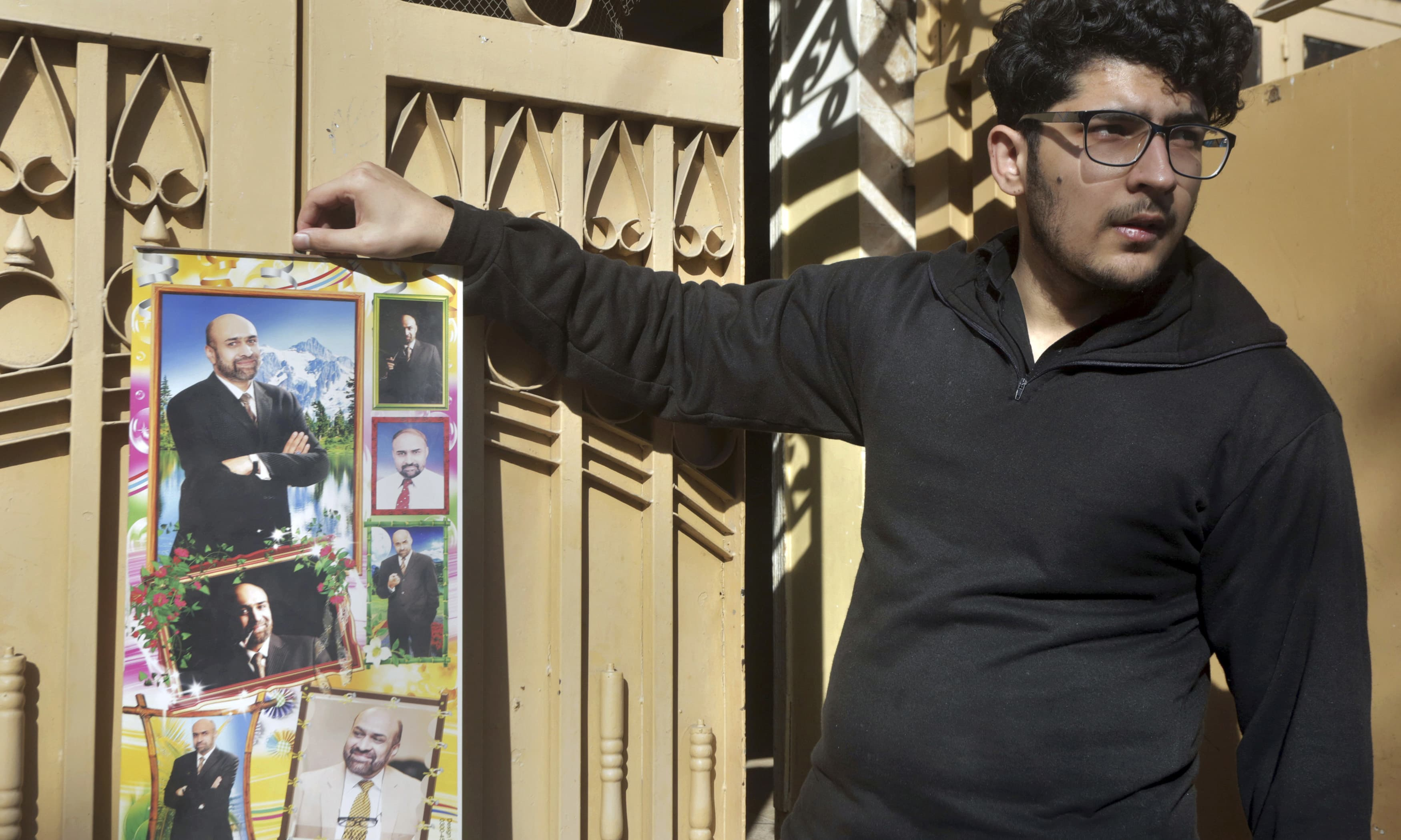 Osama Rizi, son of a journalist Rizwan-Rehman, displays a calendar with the pictures of his father outside his residence in Lahore. —AP