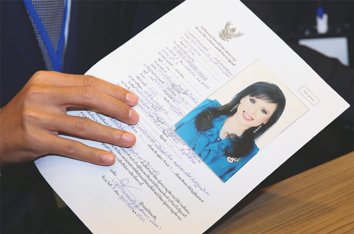BANGKOK: Thai Raksa Chart party leader Preechapol Pongpanich holds up the application form of candidate for Prime Minister, Thailand's Princess Ubolratana at the election commission office.—Reuters