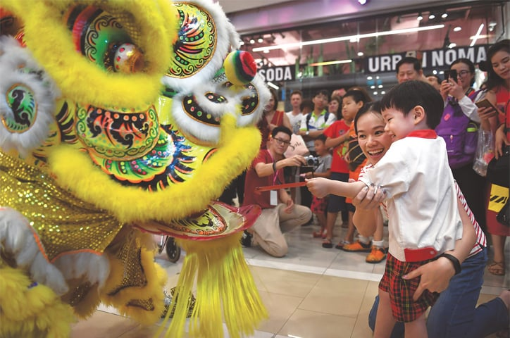 A Chinese boy gives a donation to a lion dancer in a shopping mall during Lunar New Year celebrations in Bangkok. Tourism remains the kingdom's banker, accounting for a fifth of the Thai economy. And Chinese visitors are integral — making up a quarter of Thailand's projected 41 million visitors this year.—AFP