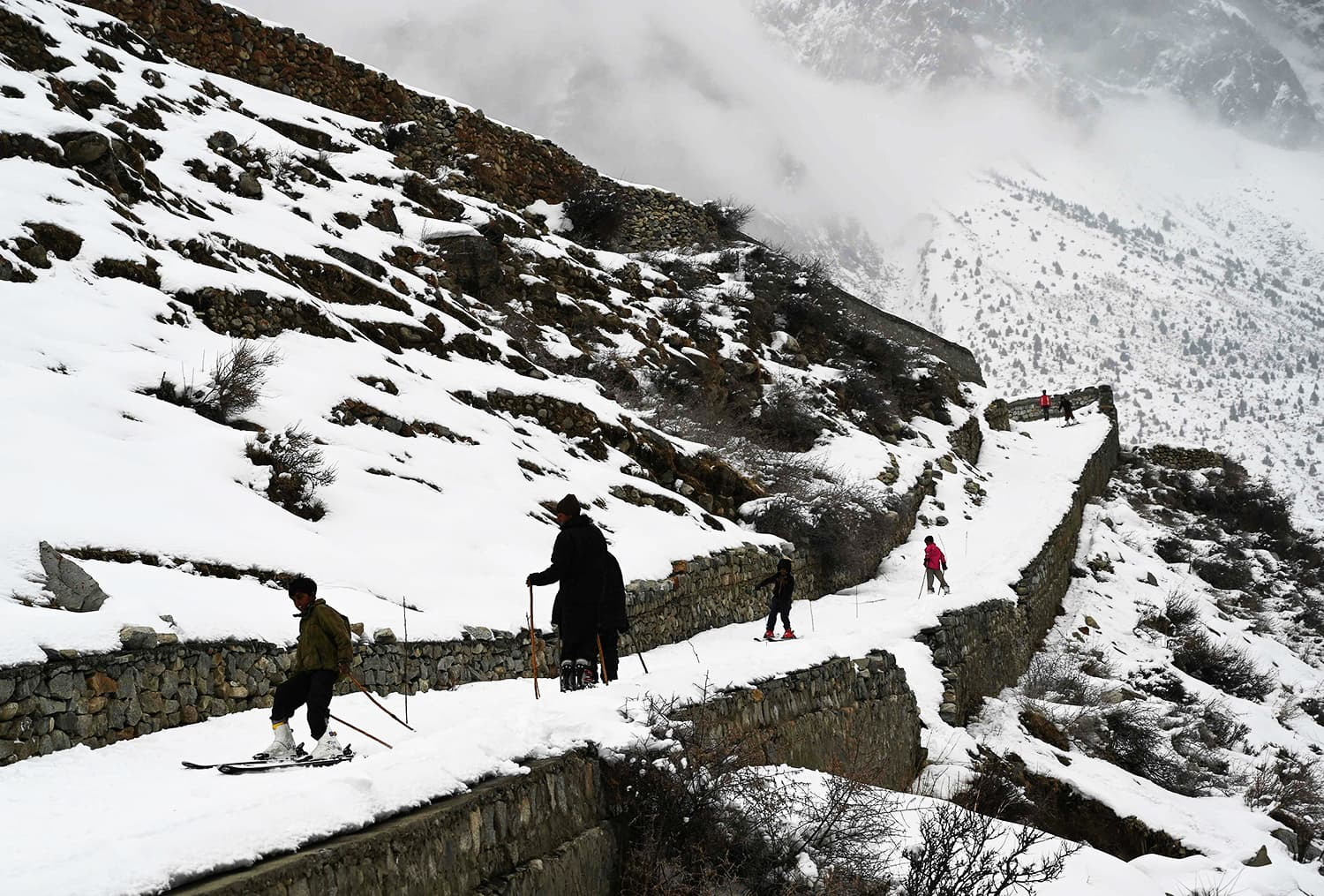 Pakistani children ski on a snow-covered street. ─ AFP