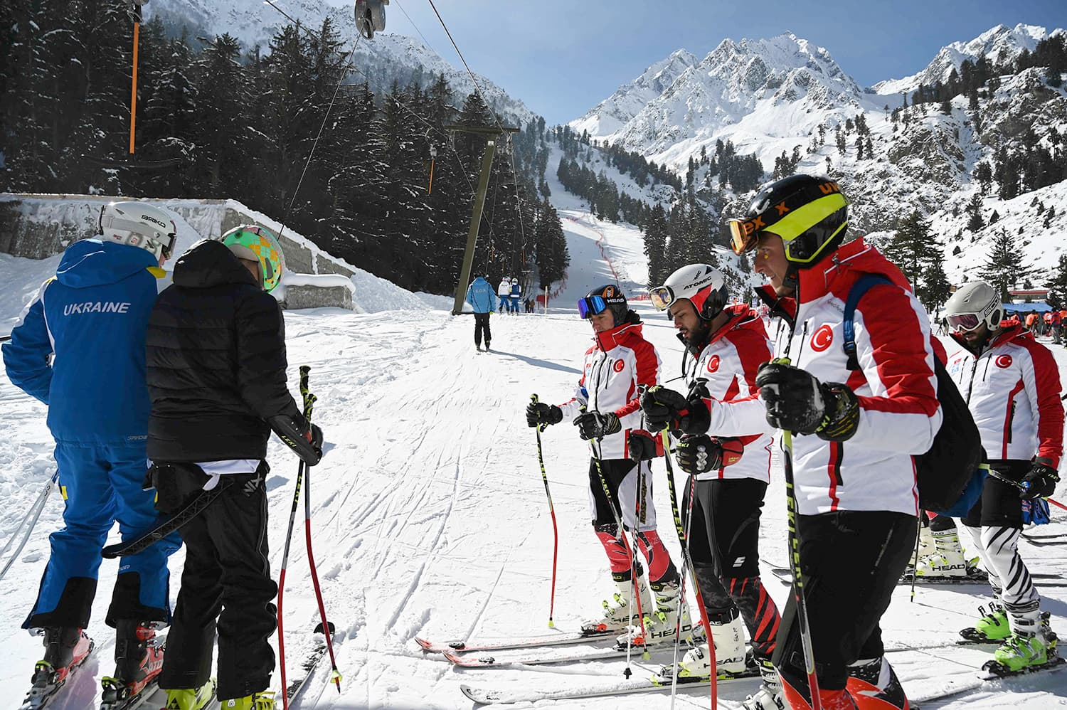 In this picture taken on January 29, 2019, Turkish and Ukrainian skiers make their way to a slope to compete in the CAS Karakoram International Alpine Ski Cup, at the Pakistan Air Force-owned and operated Naltar Ski Resort, some 25km north of Gilgit in Pakistan's remote mountainous north. - Dozens of skiers in late January took part in a rare international competition in Pakistan, which boasts some of the world's highest mountains but remains off-piste for most winter sportsmen due to years of insecurity and lack o