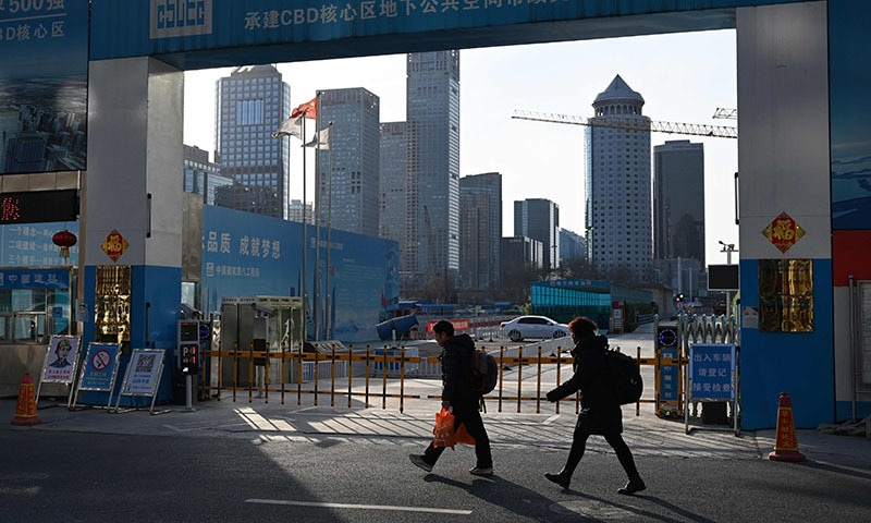 People walk past the entrance to a construction site in Beijing on February 11, 2019. — AFP