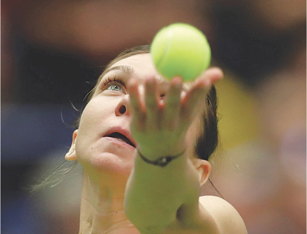 OSTRAVA: Romania's Simona Halep serves to Karolina Pliskova of the Czech Republic during their Fed Cup match at the Ostravar Arena.—Reuters