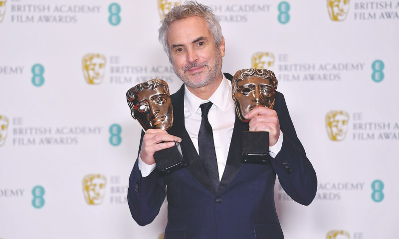 LONDON: Alfonso Cuaron poses with the awards for best director and best film for Roma.—AFP