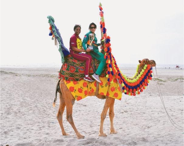 Merissa Aguilleira and Bismah Maroof on a camel at Karachi beach
