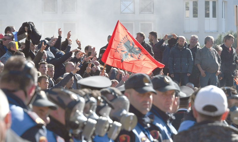 Tirana: Opposition supporters wave the national flag as police throw tear gas during a protest in front of government building, demanding the resignation of Prime Minister Edi Rama on Saturday.—AFP