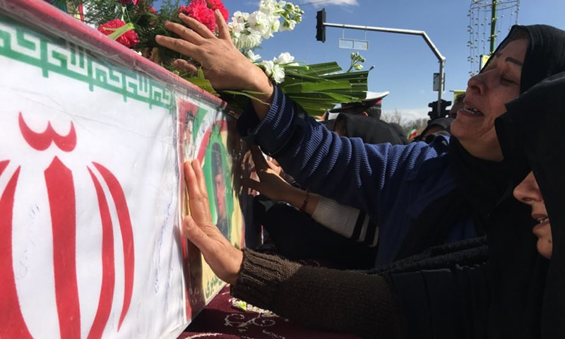 Mourners in Isfahan on February 16 reach out to touch the caskets of those killed in a suicide car bombing that targeted members of Iran's powerful Revolutionary Guards.— AP