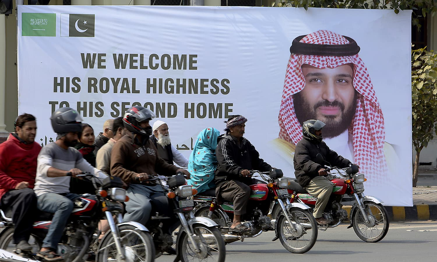 Motorcyclists pass by a banner welcoming Saudi Arabia's Crown Prince Mohammed bin Salman displayed on the occasion of his visit, in Lahore. ─ AP