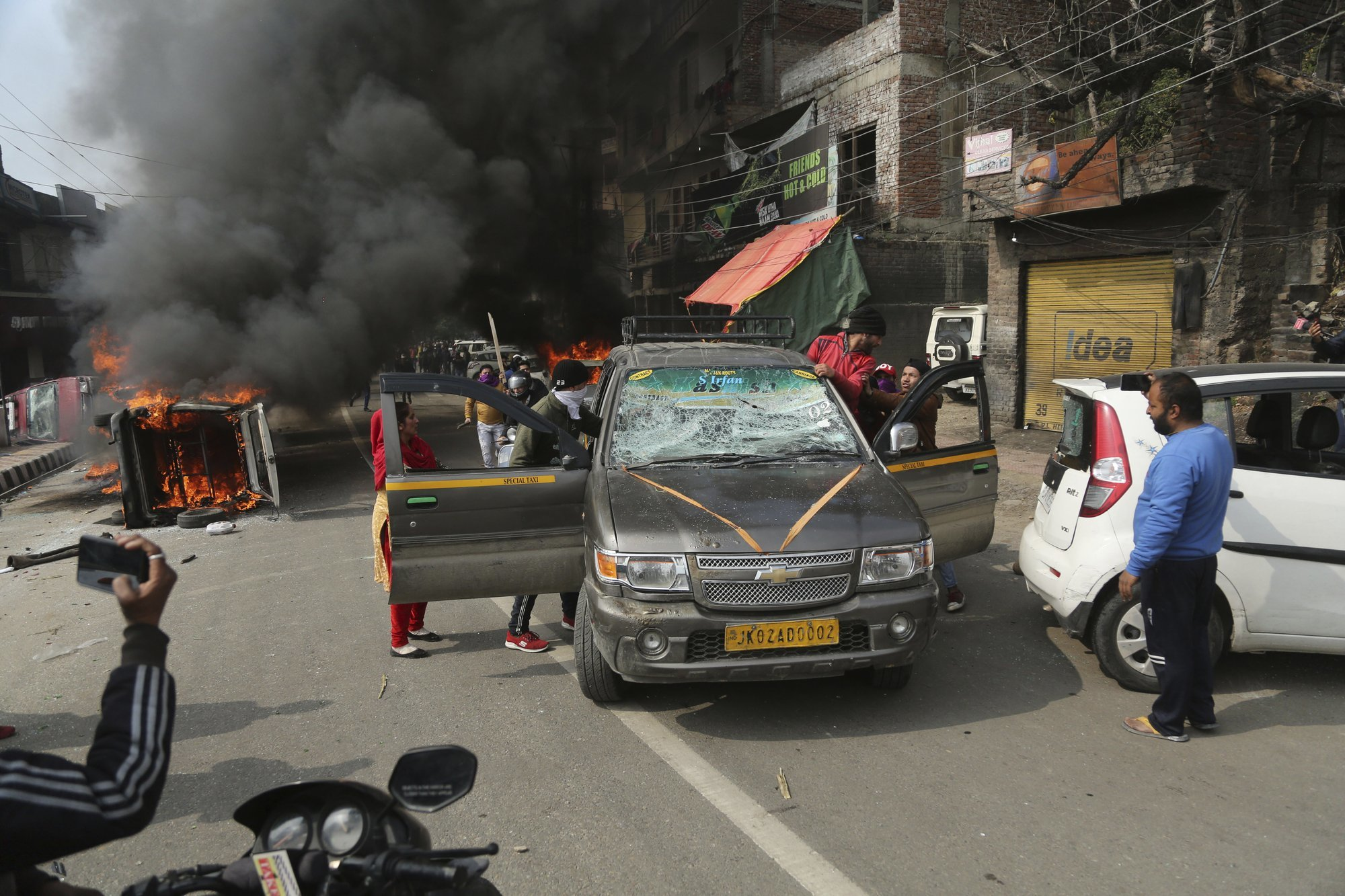 Protestors attack the driver of a vehicle during a protest against Thursday's attack on a paramilitary convoy. — AP