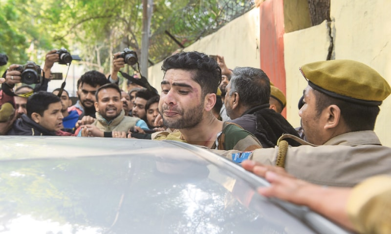 NEW DELHI: Policemen take into custody a man who was believed to be a Kashmiri and attacked by an angry mob on Sunday because he was raising anti-India slogans.—AFP