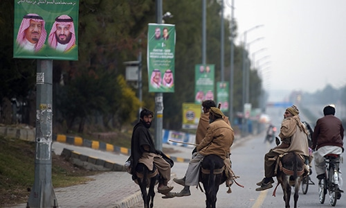 Labourers ride past welcoming posters featuring the portrait of Saudi Arabia's Crown Prince Mohammed bin Salman on a street in Islamabad on February. — AFP