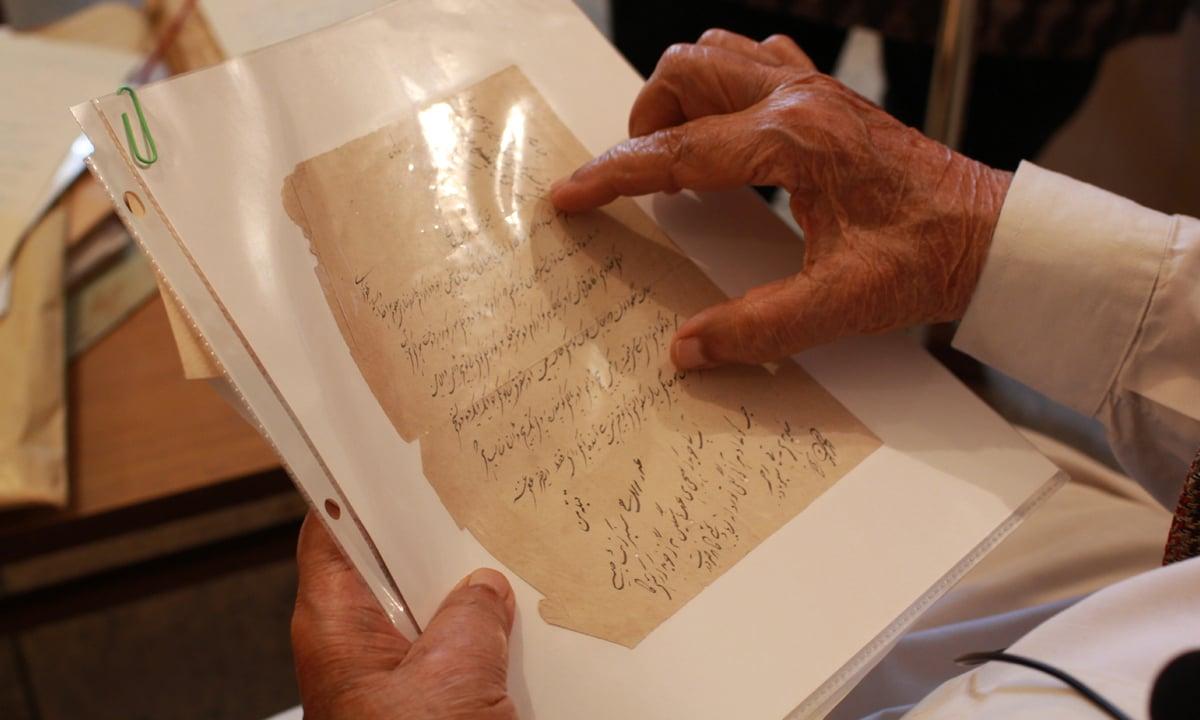 Israil Minai explaining a document written by Ameer Minai