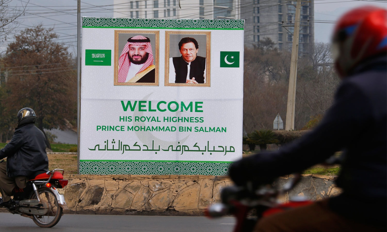 A welcoming banner featuring the portrait of the crown prince and Senate Chairman Sadiq Sanjrani is displayed on the building of the Parliament House in Islamabad. — AFP