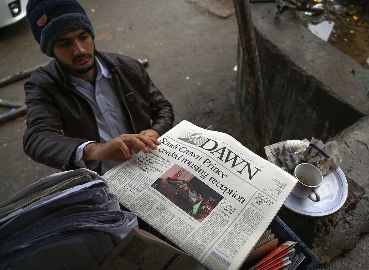 A man buys a morning newspaper with front-page-coverage of Saudi Arabian Crown Prince Mohammed bin Salman at a roadside stall in Islamabad on February 18. — AFP
