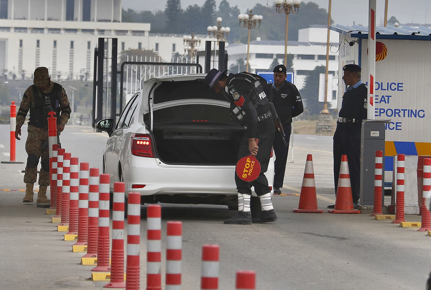 An army soldier stands guard while police officers search a vehicle at a checkpoint near presidency to ensure security ahead of MBS's visit to Pakistan, in Islamabad on February 17. — AP