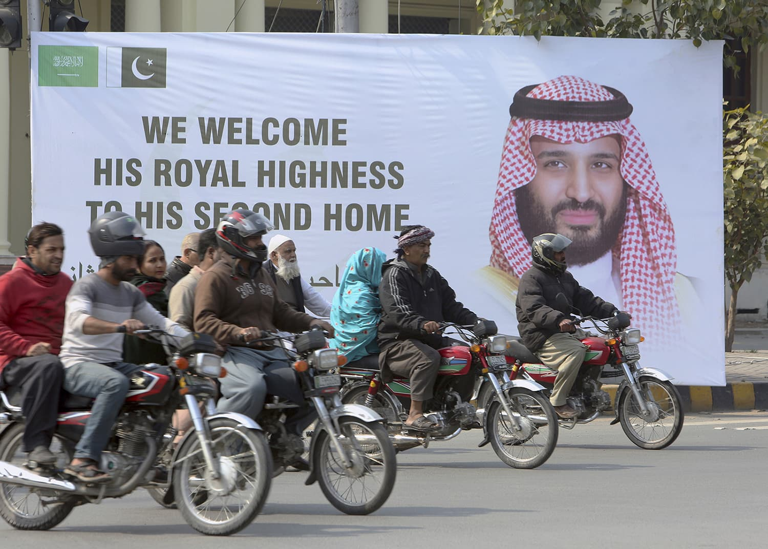Motorcyclists pass by a banner welcoming Saudi Arabia's Crown Prince Mohammed bin Salman displayed on the occasion of his visit, in Lahore on February 16. — AP