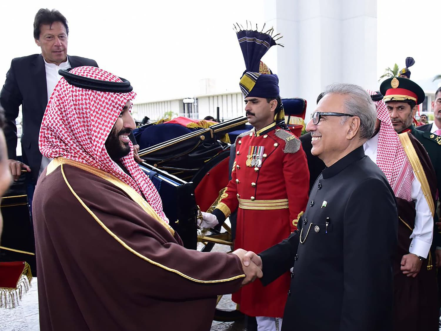 President Alvi shakes hands with the crown prince as Prime Minister Imran Khan looks on. — AFP