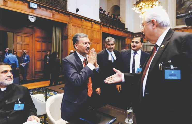 THE HAGUE: Deepak Mittal, a joint secretary in India's ministry of external affairs, avoids shaking hands with Pakistan's Attorney General Anwar Mansoor Khan and responds to the greeting by clasping his hands prior to the hearing of the case at the International Court of Justice on Monday.—AFP