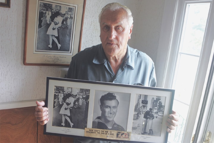 In this July 2, 2009, file photo George Mendonsa poses for a photo, holding a copy of the famous Alfred Eisenstadt photo of him kissing a woman in a nurse's uniform in Times Square on Aug 14, 1945, while celebrating the end of World War II.—AP