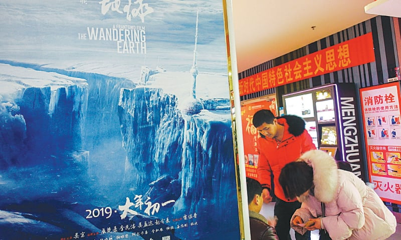 YICHANG (China): People standing beside a poster of the Chinese sci-fi blockbuster film The Wandering Earth.—AFP