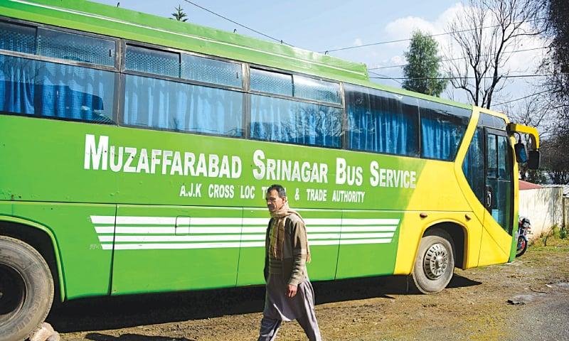 Muzaffarabad: A Kashmiri walks past a bus of the Muzaffarabad-Srinagar Bus Service, parked on a street, here on Wednesday.—AFP