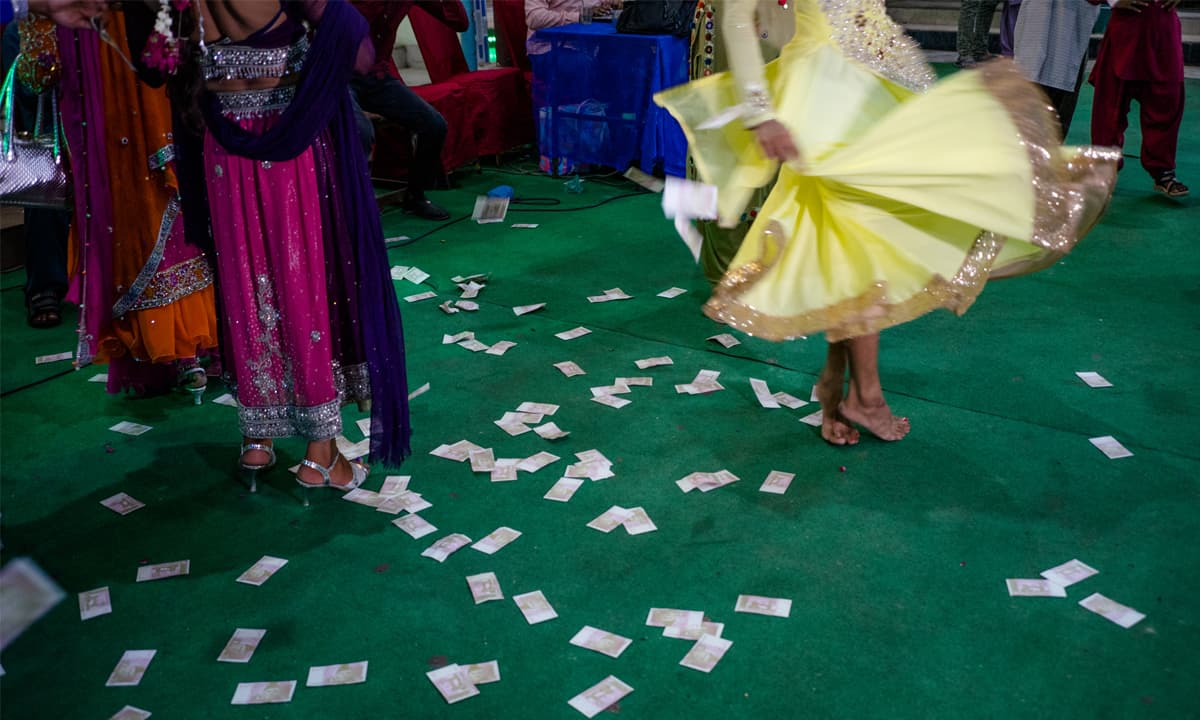 Spectators shower money on a dancing *mashooq*