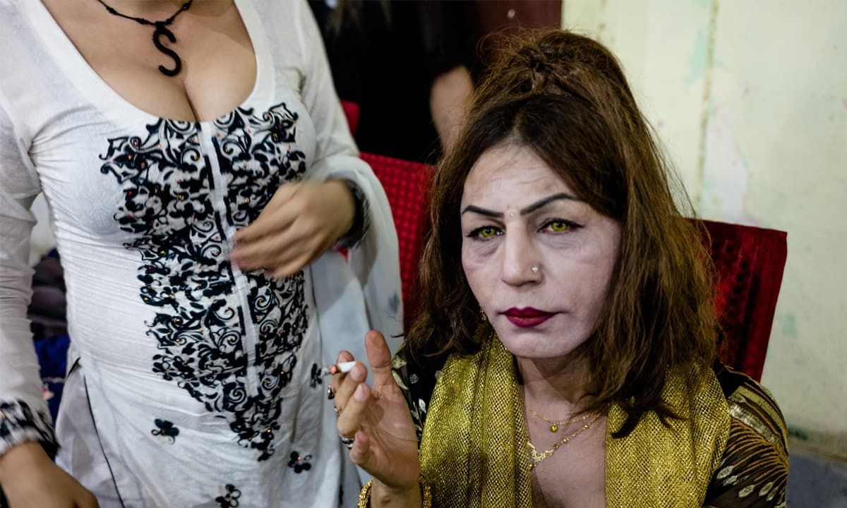 An older transwoman smokes a cigarette at a function in Karachi