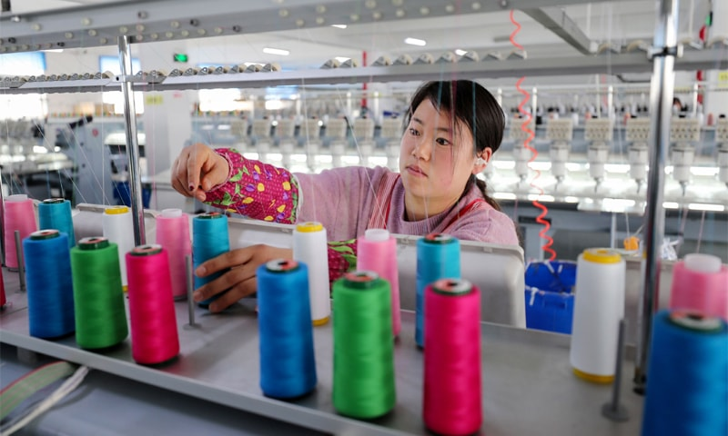 An employee works at a textile factory in Lianyungang in China's eastern Jiangsu province on Thursday.—AFP