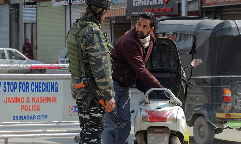 An Indian Central Reserve Police Force (CRPF) personnel searches a Kashmiri man and his scooter next to a road sign asking to stop for checking in Srinagar on February 24, 2019.  — AFP