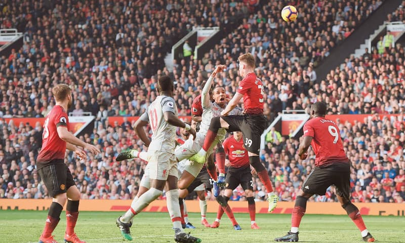MANCHESTER: Liverpool's Joel Matip (C) vies with Manchester United's Scott McTominay (second R) during their Premier League match at Old Trafford on Sunday.—AFP