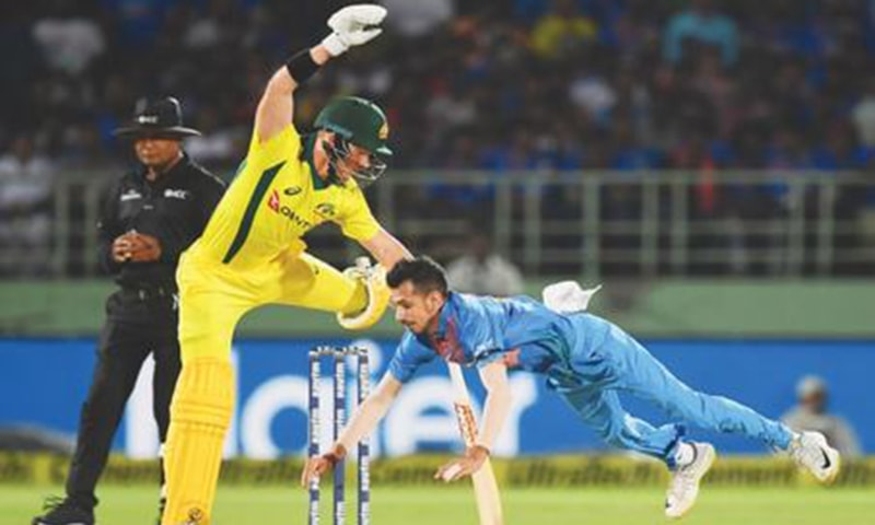 VISAKHAPATNAM: Indian spinner Yuzvendra Chahal dives to attempt a catch off his own bowling as Australian opener D'arcy Short jumps to avoid the ball during the first T20 International on Sunday.—AFP