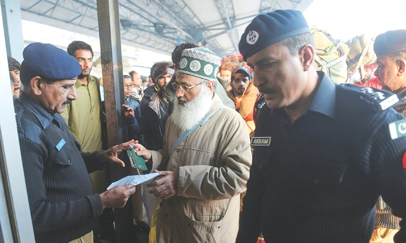 LAHORE: Police officers check documents of passengers travelling to India on board the Samjhota Express at the Lahore railway station on Monday.—AFP