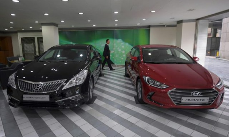 A man walks past Hyundai cars at a dealership of Hyundai Motor.— AFP/File