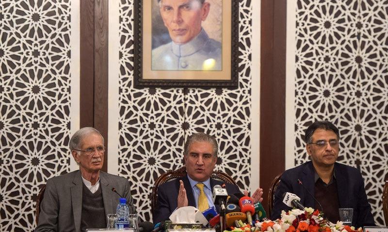 وزیر خارجہ شاہ محمود قریشی پریس کانفرنس سے خطاب کر رہے ہیں، ان کے ساتھ وزیر خزانہ اسد عمر اور وزیر دفاع پرویز خٹک بھی موجود ہے— فوٹو: اے ایف پی