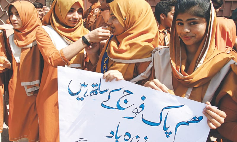 Jubilant crowds dance to drumbeats in Jacobabad and schoolgirls in Hyderabad share sweets to celebrate downing of two Indian jets by Pakistan Air Force on Wednesday.—Dawn