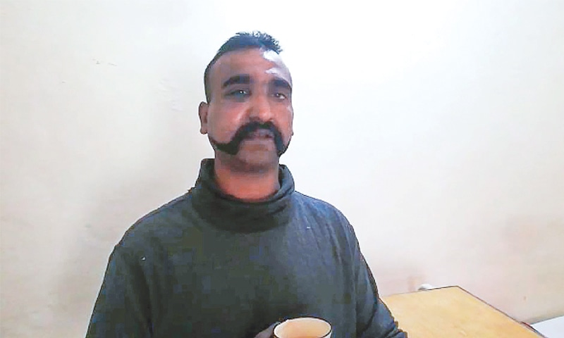 The handout photograph released by Inter-Services Public Relations shows the captured Indian pilot, holding a cup of tea, in the custody of Pakistani forces at an undisclosed location.—AFP